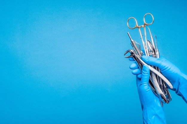 Hand in blauwe handschoen met chirurgische tandheelkundige instrumenten op lichtblauwe achtergrond