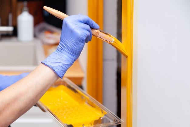 Hand in blauwe rubberen handschoen met penseel schilderij natuurlijke houten deur met gele verf