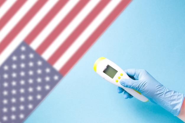Hand in blauwe wegwerp rubberen handschoen houdt infrarood contactloze thermometer tegen blauw oppervlak