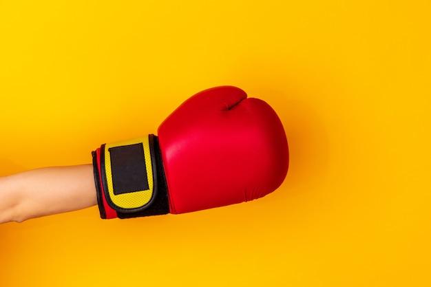 Hand in boksen, bokser rode handschoen geïsoleerd op gele studio achtergrond met copyspace. schoppen, vasthouden, vechten aan de zijkant. negatieve ruimte voor uw reclame. sport, advertentie, activiteit, competitie.
