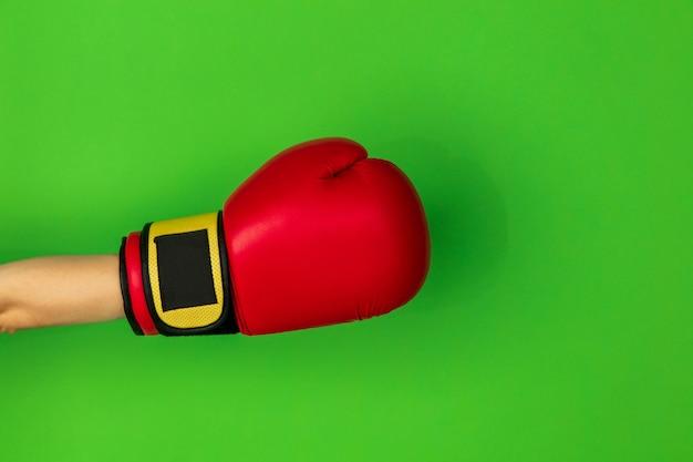 Hand in boksen, bokser rode handschoen geïsoleerd op groene studio achtergrond met copyspace. schoppen, vasthouden, vechten aan de zijkant. negatieve ruimte voor uw reclame. sport, advertentie, activiteit, competitie.
