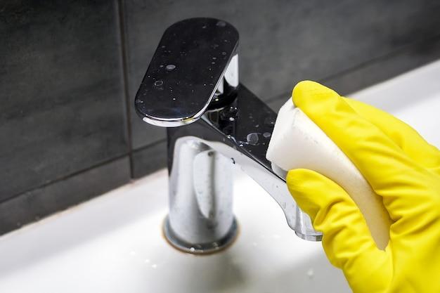 Hand in een gele rubberen handschoen veegt een vuile verchroomde metalen kraan af