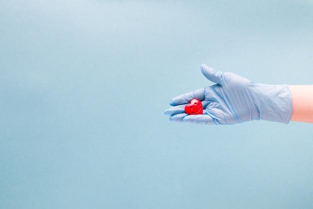 Hand in een handschoen houdt een klein rood lachend hartje vast