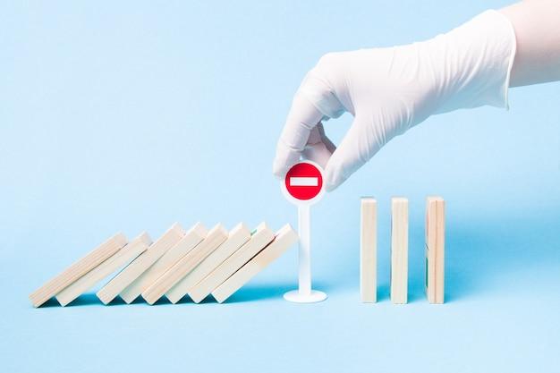 Hand in een medische rubberen handschoen voorkomt dat een domino valt met behulp van een miniatuur stopbord van plastic speelgoed