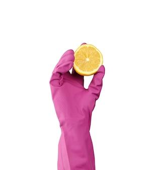 Hand in een roze latex schoonmaak handschoen houdt een halve citroen op een witte achtergrond, close-up