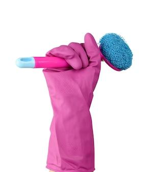 Hand in een roze rubberen handschoen voor het schoonmaken van een huis houdt plastic borstel met een handvat op een witte achtergrond, close-up