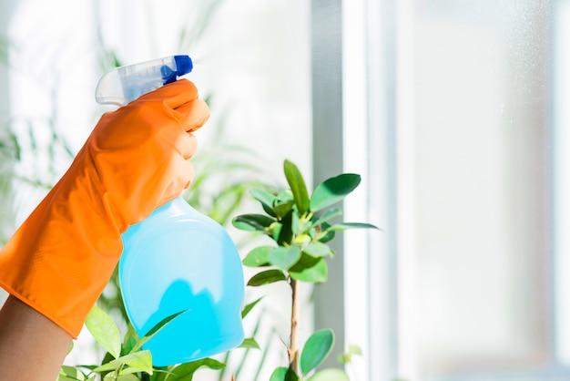 Hand in een rubberen handschoen houdt spuitfles vloeibaar wasmiddel