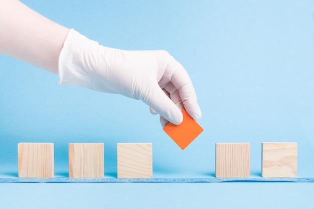 Hand in een rubberen wegwerp witte medische handschoen neemt een rood blok een houten vierkant, dominostenen staan op een rij, blauw oppervlak