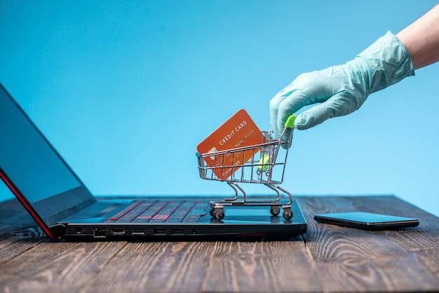 Hand in een steriele handschoen houdt een winkelwagentje met een creditcard. aankopen via internet tijdens de pandemie van het coronavirus