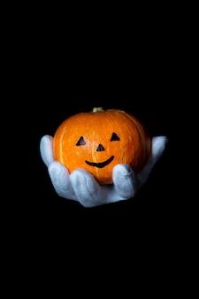 Hand in een witte handschoen houdt een pompoen op een zwarte achtergrond