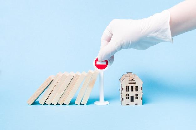 Hand in een witte medische rubberen handschoen stopt een domino met behulp van een miniatuur stopbord