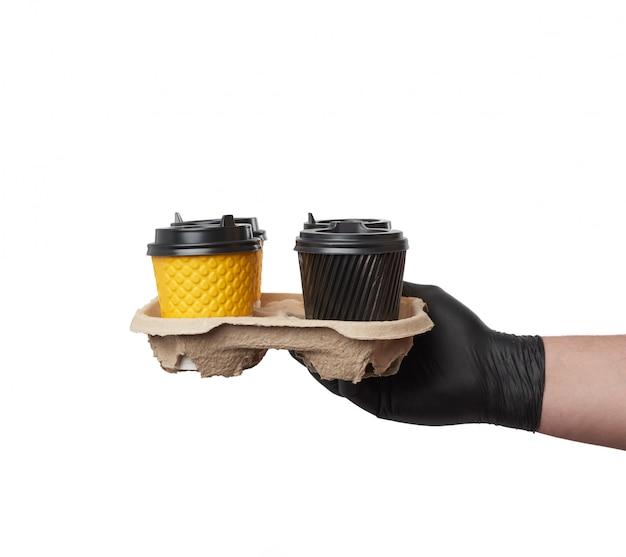 Hand in een zwarte latex handschoen houdt een papierlade met wegwerp c