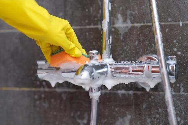 Hand in gele handschoen wast verchroomde mixer met washandje in badkamer