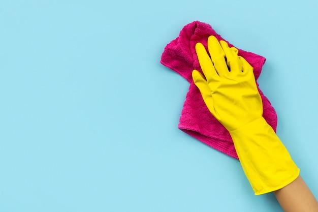 Hand in gele rubberen handschoen afvegen door vod blauwe achtergrond. schoonmaakservice of huishouding