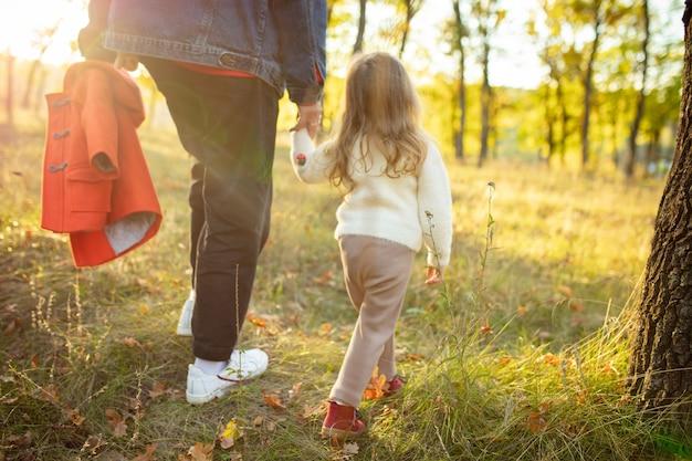 Hand in hand, bijgesneden. gelukkige vader en kleine schattige dochter wandelen langs het bospad in zonnige herfstdag. familietijd, saamhorigheid, ouderschap en gelukkig kindertijdconcept. weekend met emoties.