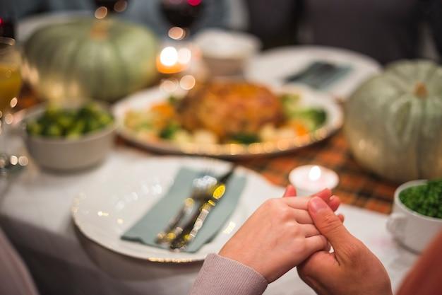 Hand in hand in de buurt van tabel met voedsel