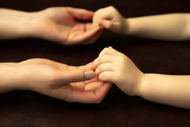 Hand in hand, klappend als vrienden. close-up shot van de handen van vrouwen en kinderen die verschillende dingen samen doen. familie, huis, onderwijs, jeugd, liefdadigheidsconcept. moeder en zoon of dochter, rijkdom.
