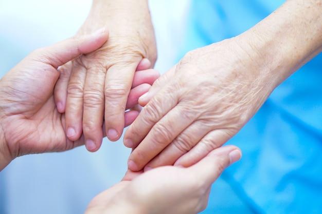 Hand in hand met aziatische senior patiënt met liefde