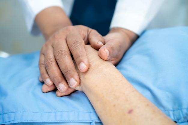 Hand in hand senior vrouw patiënt