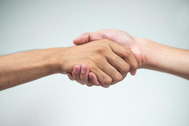 Hand in hand van twee mannen op een witte ondergrond