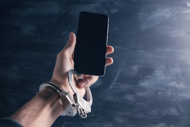 Hand in handboeien houdt een telefoon op een grijs