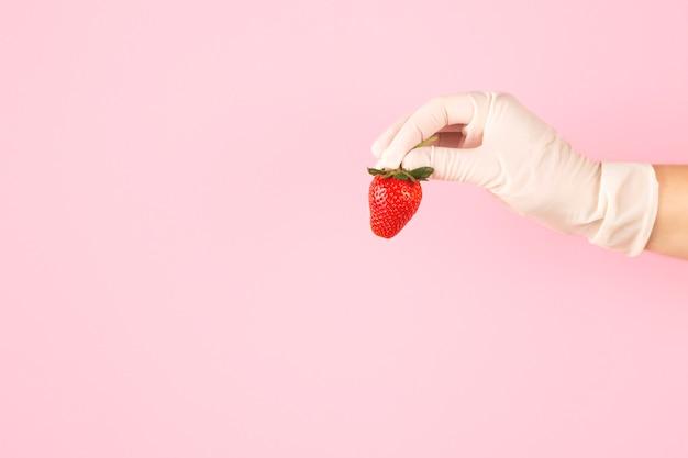 Hand in handschoen houdt aardbeien op een roze achtergrond.
