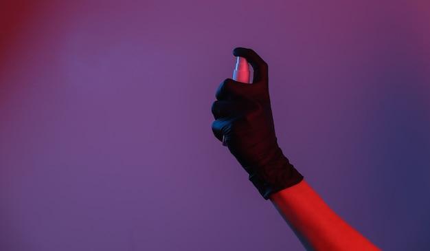 Hand in handschoen houdt antiseptische spray vast. rood-blauw neonlicht