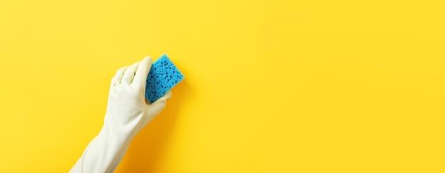 Hand in handschoen met een reinigingsspons over gele achtergrond, panoramische lay-out met ruimte voor tekst