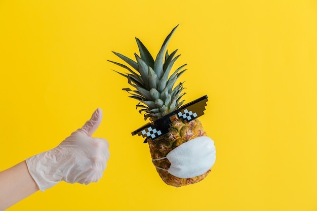 Hand in handschoen toont duimen omhoog teken. zwevende ananas met grappig gezicht met een bril en een beschermend medisch masker. reizen coronavirus concept. tropisch fruit ananas op gele zomer achtergrond.