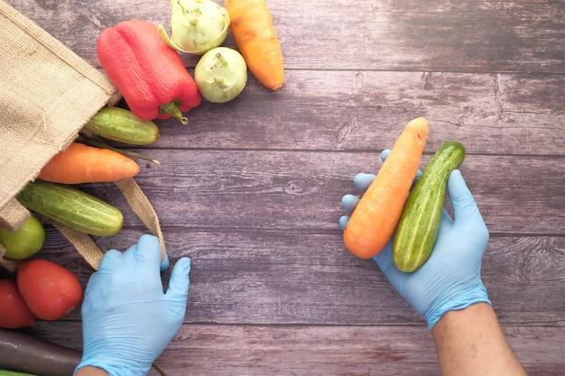 Hand in handschoenen nemen groente uit een herbruikbare zak groenten bovenaanzicht