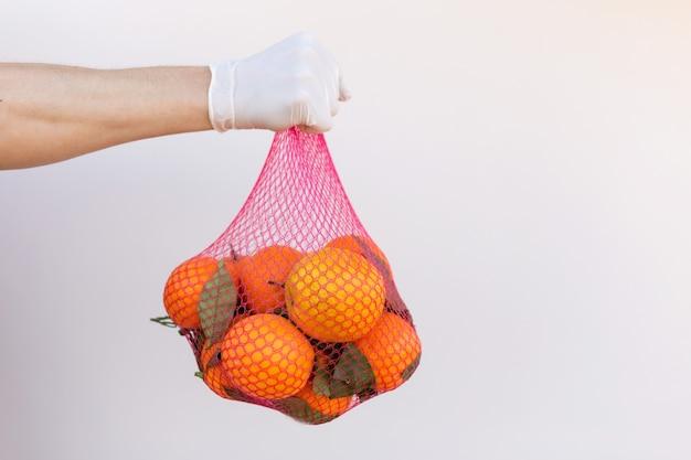 Hand in latex handschoen met tas. citrusvruchten in een raster van natuurlijke materialen op een witte achtergrond met plaats voor tekst. eco-verpakking. helder oranje mandarijnen. natuurlijk licht. vitaminen tijdens pandemie.