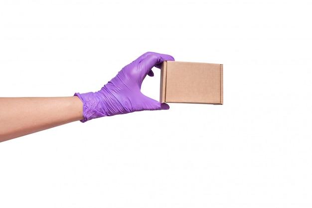 Hand in latex handschoenen met kartonnen doos