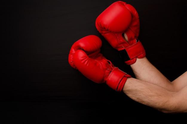 Hand in rode bokshandschoenen in de hoek van het frame op een zwarte muur, lege ruimte