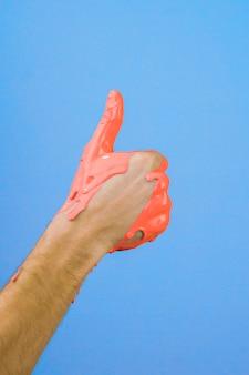 Hand in rode verf duim omhoog op blauwe achtergrond