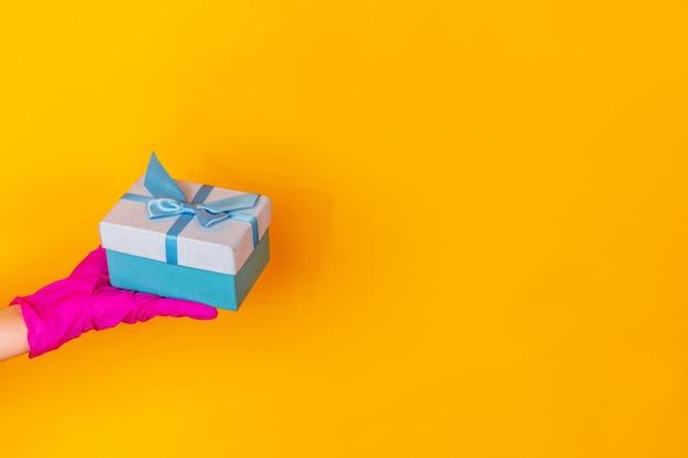 Hand in roze beschermende rubberen handschoen met cadeau geïsoleerd op gele studio achtergrond met copyspace. gebaren, vasthouden, dingen presenteren. negatieve ruimte voor uw reclame. tonen, wijzen.