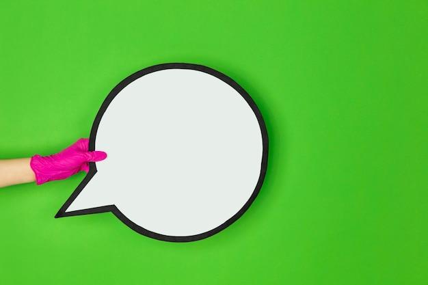 Hand in roze beschermende rubberen handschoen met commentaar geïsoleerd op groene studio achtergrond met copyspace. gebaren, vasthouden, dingen presenteren. negatieve ruimte voor uw reclame. tonen, wijzen.