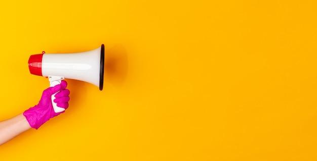 Hand in roze beschermende rubberen handschoen met megafoon geïsoleerd op gele studio achtergrond met copyspace. gebaren, vasthouden, dingen presenteren. negatieve ruimte voor uw reclame. tonen, wijzen.