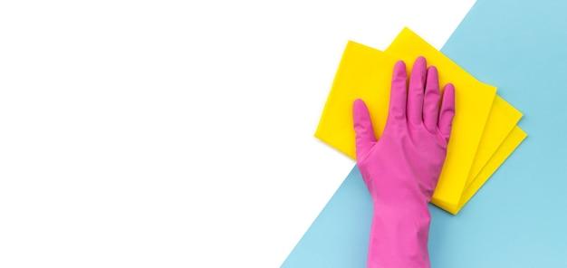 Hand in roze rubberen handschoen afvegen door lap blauwe achtergrond. schoonmaakservice of huishouding