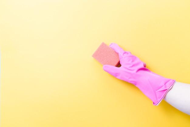 Hand in roze rubberen handschoen houdt oranje spons voor afwassen en schoonmaken