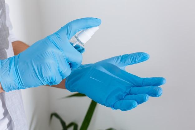Hand in rubberen chirurgische handschoenen met antiseptische handdesinfecterend middel op de achtergrond. alcoholdesinfecterende middelen of gel voor handhygiëne corona virusbescherming. antibacteriële vloeistof tegen covid-19
