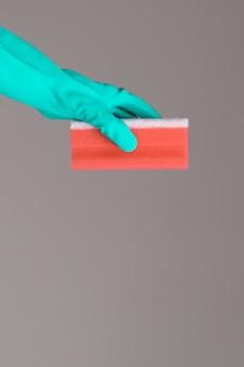 Hand in rubberen handschoen houdt kleur was spons op neutraal oppervlak. het concept van de heldere lente.