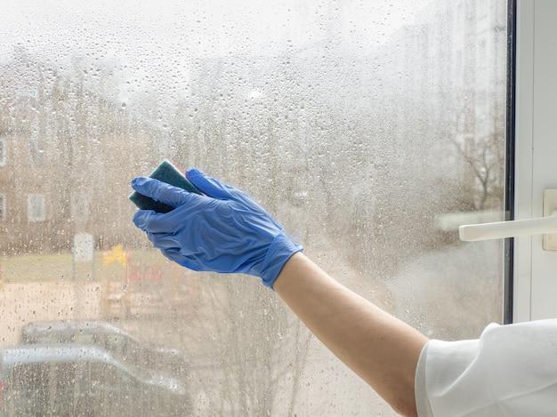 Hand in rubberen handschoenen desinfecteert ramen met ontsmettingsmiddel en spons