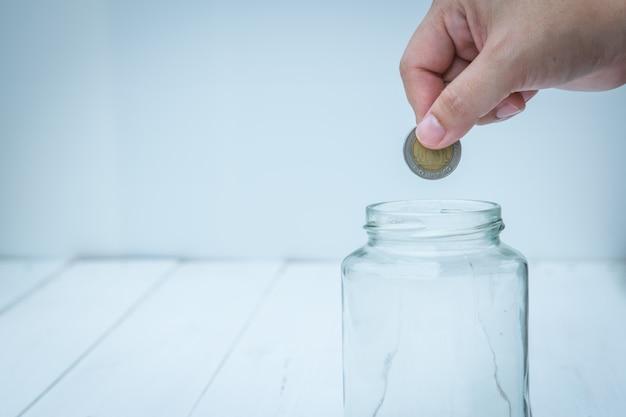 Hand indienen munt in de lege glazen fles