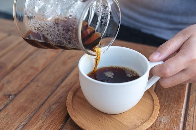 Hand infuus koffie gieten in een witte mok op vintage houten tafel