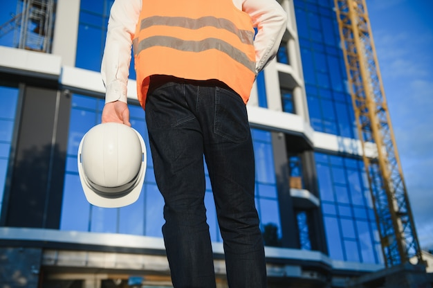 Hand ingenieur werknemer met veiligheidshelm met gebouw op de achtergrond van de site.