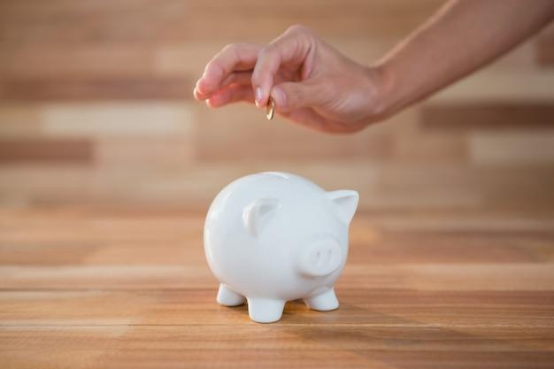 Hand invoegen van muntstuk in spaarvarken