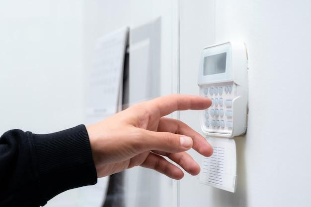 Hand invoeren van het wachtwoord van het alarmsysteem van een appartement, huis of kantoor. bewakings- en beschermingsconsole tegen rubberachtig en dief