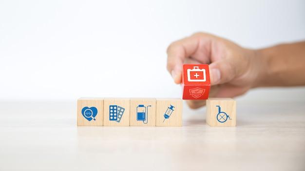 Hand kies medische tas pictogram op houten blokken.