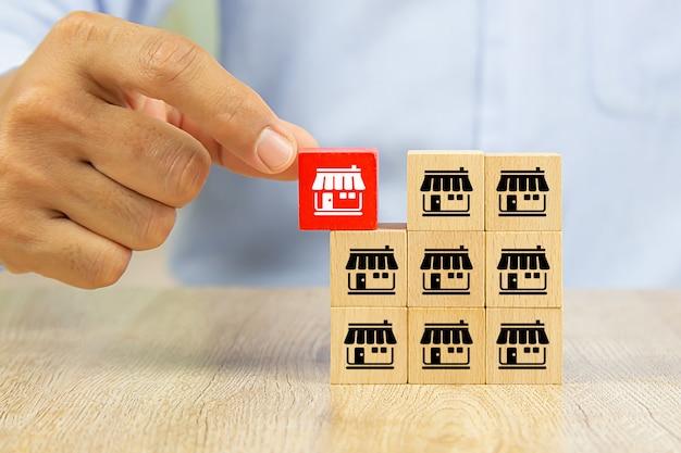 Hand kies rode kleur houten speelgoed blok gestapeld met franchise marketing iconen