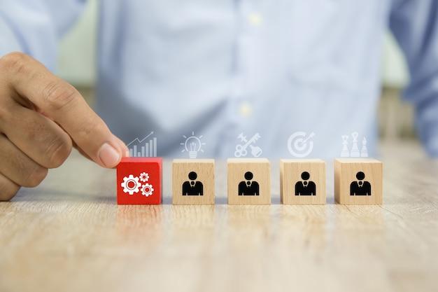 Hand kies versnellingspictogram met zakenman op kubus houten blokstapel.